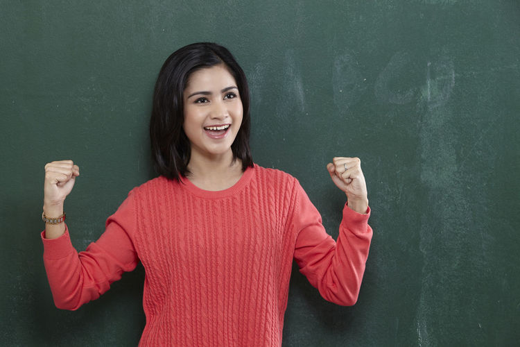 Cheerful female teacher gesturing while standing by blackboard