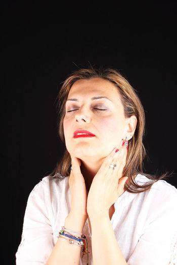 Close-Up Of Woman With Eyes Closed Touching Neck Against Black Background