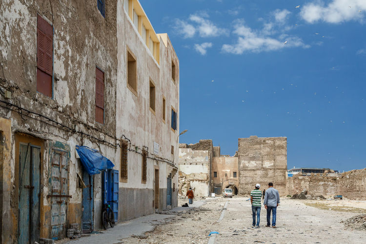 Men walking on footpath by old buildings in town