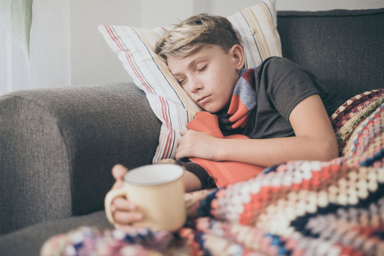 Ill boy having drink in cup while lying on sofa at home