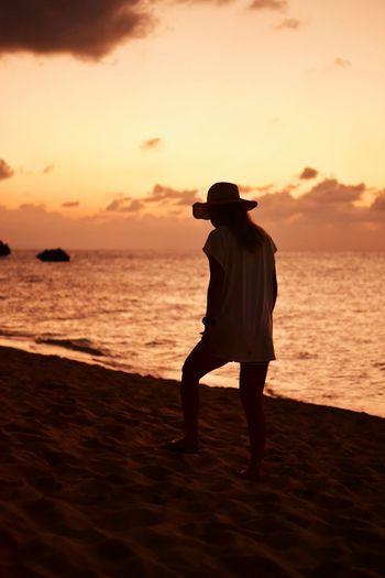 Full length of silhouette man standing on beach against sky during sunset