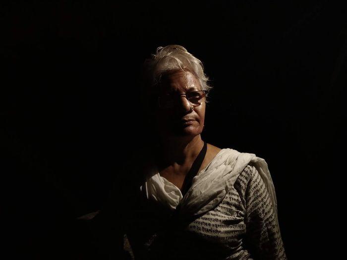 Portrait of mid adult woman against black background..