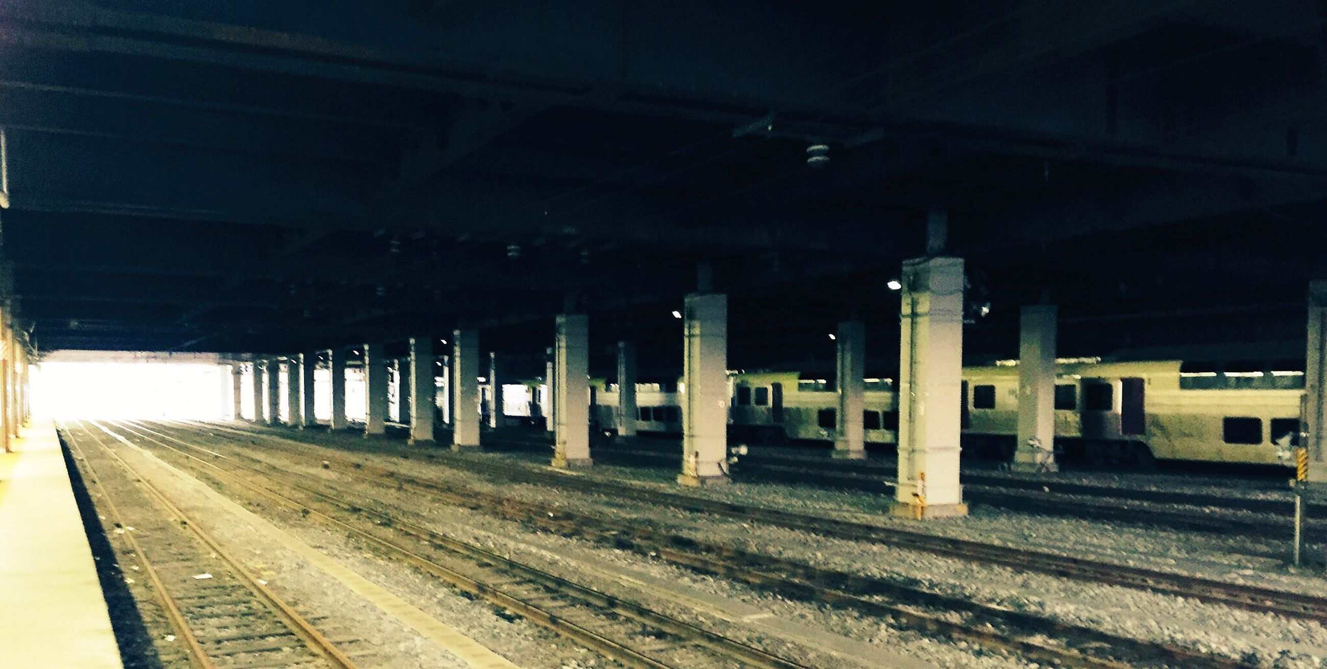 railroad track, built structure, architecture, public transportation, architectural column, the way forward, diminishing perspective, illuminated, empty, no people, column, outdoors, sky, vanishing point