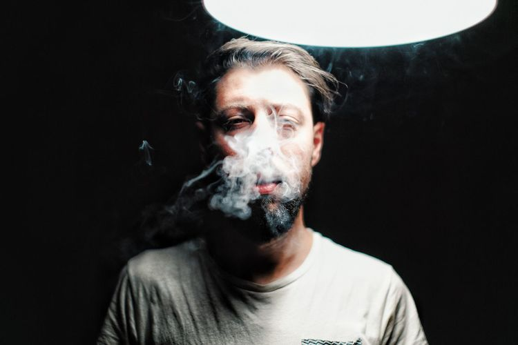 Portrait of man smoking cigarette against black background