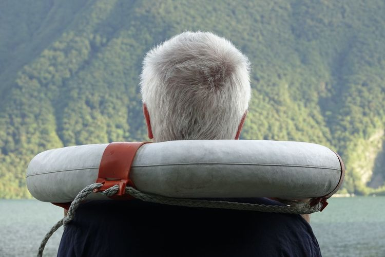 Rear View Of Man With Life Belt By River