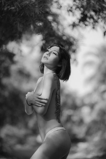 Topless woman standing against trees