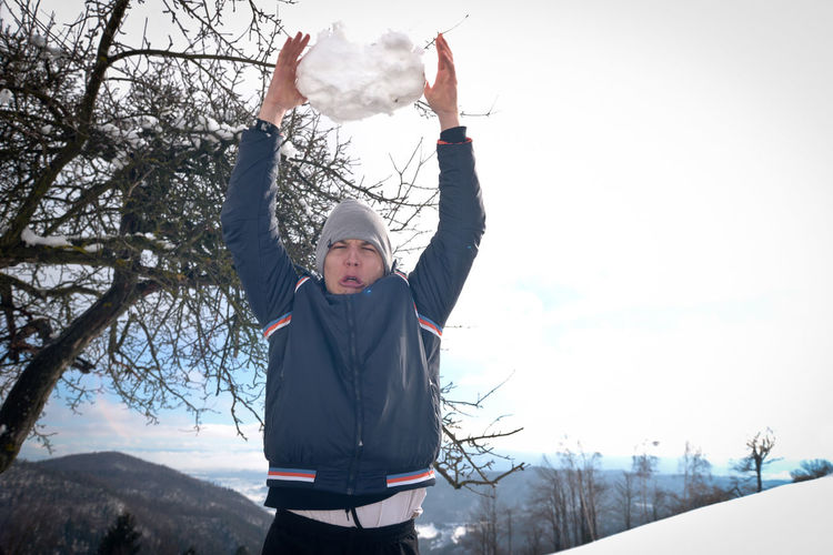 Man Making Face While Throwing Big Snowball During Winter Outdoors