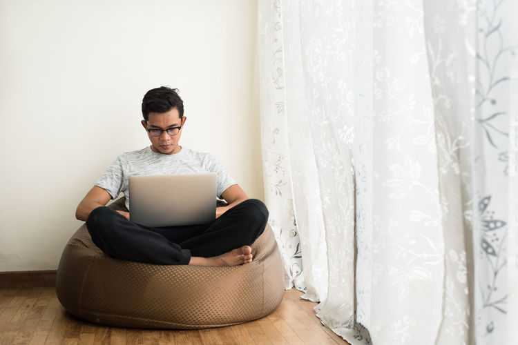 Young Man Using Laptop While Sitting On Bean Bag By Window At Home