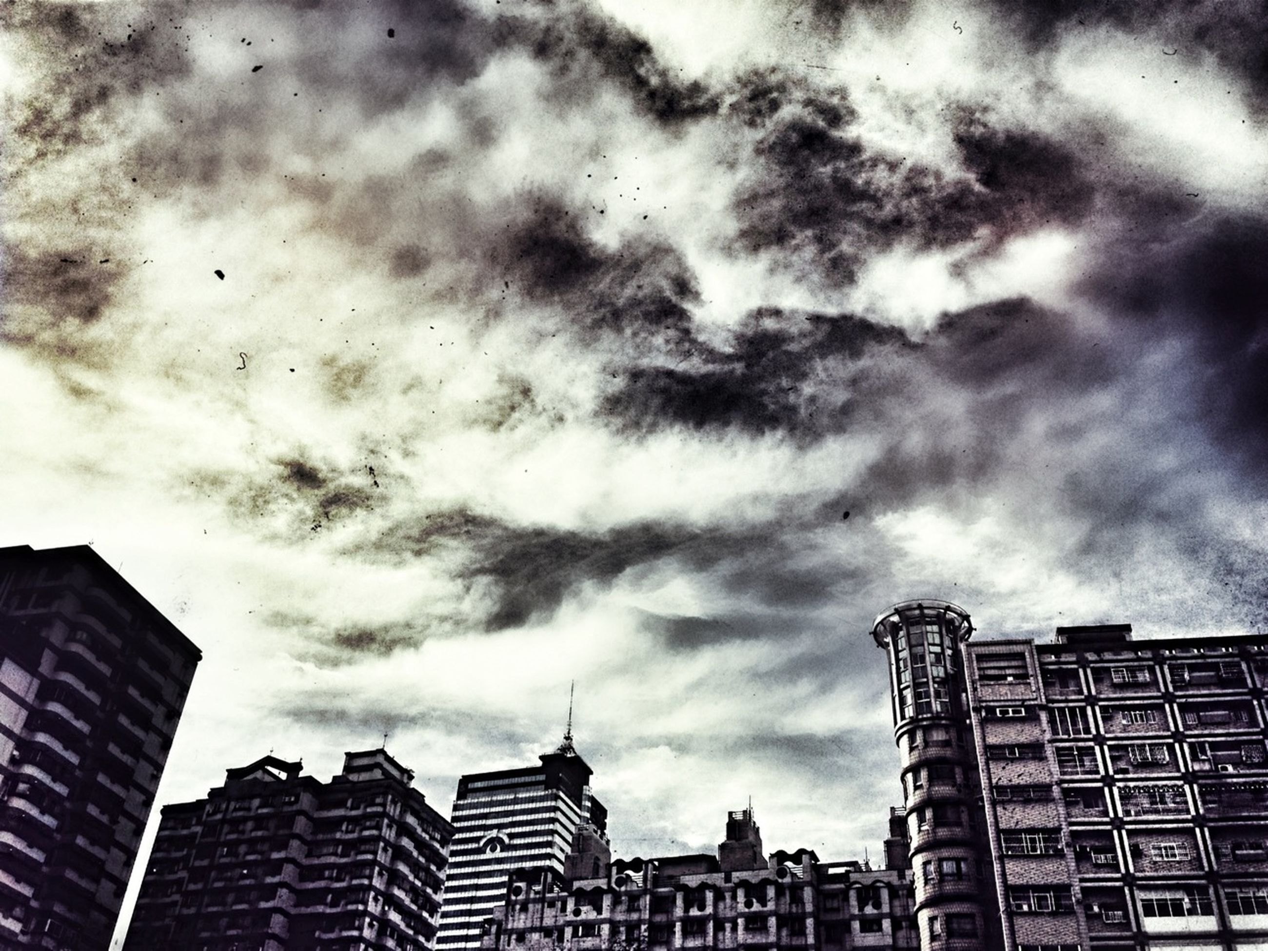 building exterior, architecture, built structure, sky, city, low angle view, cloud - sky, cloudy, building, skyscraper, residential building, cloud, overcast, residential structure, modern, office building, tall - high, weather, outdoors, city life
