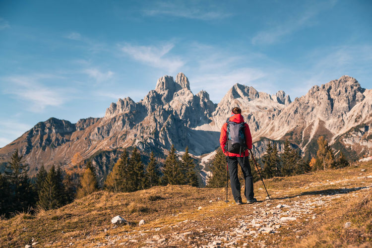 Rear view of woman hiking in forest against sky during winter