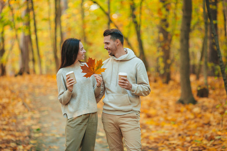 Man and woman wearing mask in forest during autumn