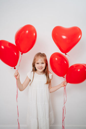 Portrait of smiling girl with red balloons against white background