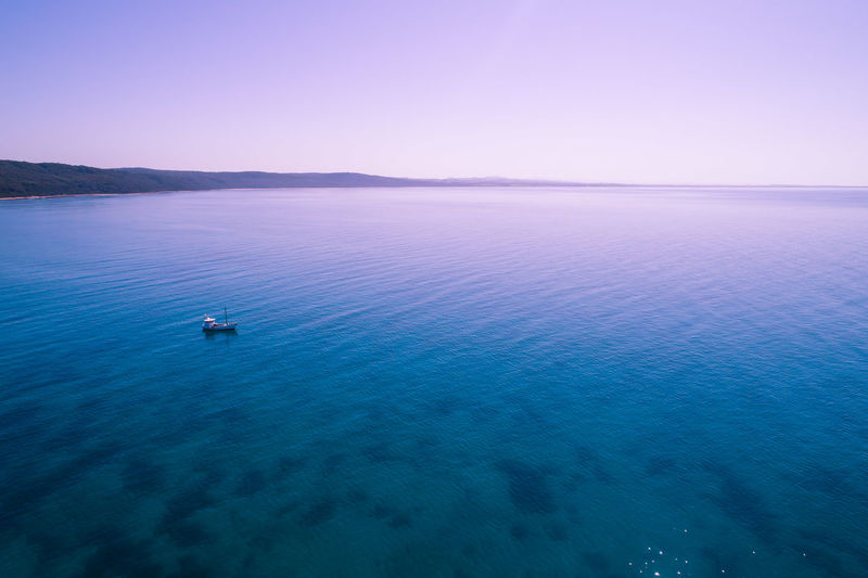 Lone fishing boat in shallow ocean bay waters at walkerville, victoria, australia with copy space