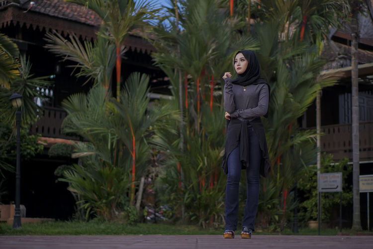 Full length of thoughtful young woman wearing hijab while standing against plants