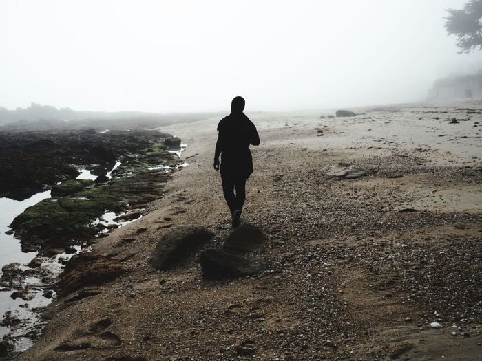 Silhouette man walking at beach during foggy weather
