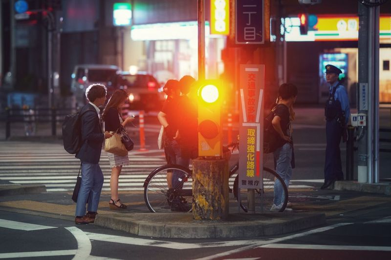 People crossing road in city at night