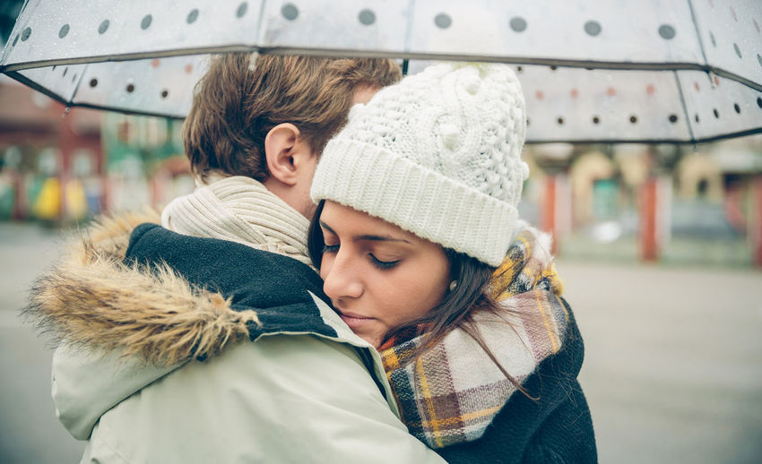 Closeup of young beautiful couple embracing under the umbrella in an autumn rainy day. Love and couple relationships concept. Woman Cold Winter Hat Scarf Horizontal Rain Girl Young Female Outdoors Fall Real People Caucasian Two People Couple Love Realtionship Man Male Umbrella Rainy Happy Embracing Hugging
