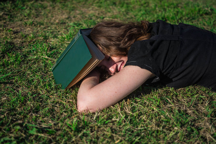 Young woman lying down in the grass with a book. One Person Nature White Woman Young Adult Portrait Curly Hair Freckles Black Dress Caucasian Candid Real People Smart Intelligent Intelligence Lifestyle Reading Green Nap Sleeping Lying Down Resting Relaxing Outdoors Tranquility Sunny Day Beautiful Book Grass Land Relaxation Day Boring Bored Boredom Leisure Activity Smile Laughing Studying Learning The Portraitist - 2019 EyeEm Awards