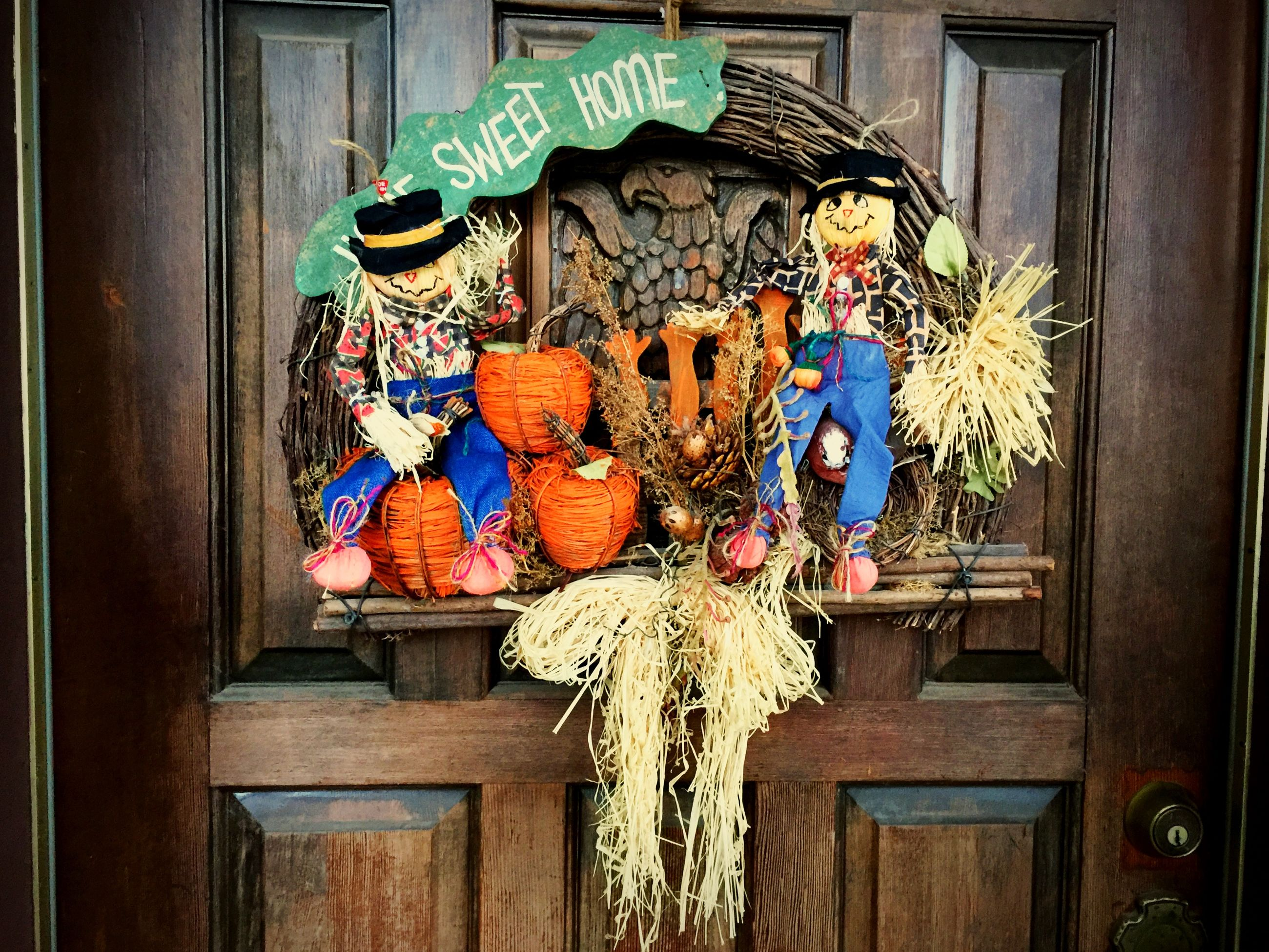 flower, decoration, hanging, art and craft, wood - material, art, creativity, built structure, building exterior, architecture, window, house, door, wall - building feature, low angle view, multi colored, ornate, human representation, religion