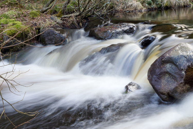 Blurred Motion Of Water Flowing Amidst Rocks In River