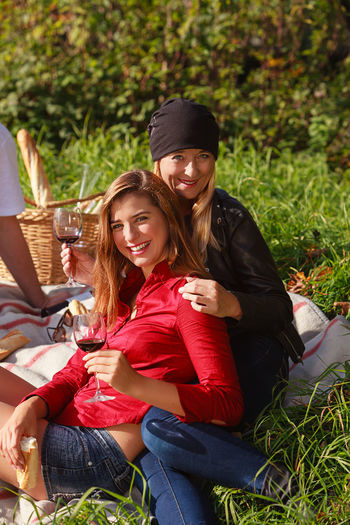 Portrait of smiling female friends sitting on grassy land in park