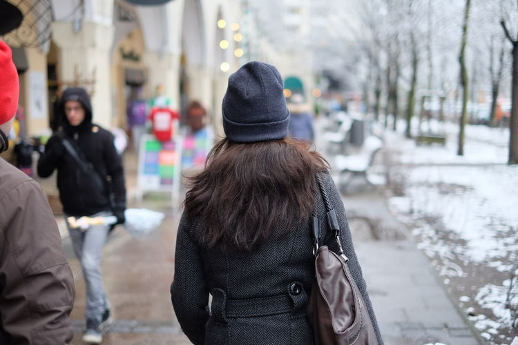 Rear view of woman in knit hat and jacket walking on footpath