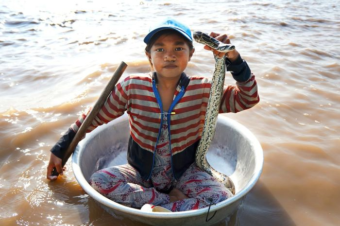 Whilst visiting Cambodia this fearless young girl paddled over to me and asked if I would like to hold her snake for $1. I declined and instead asked for a photo of her holding the snake for $1. Exploitation is always a fierce debate, but who was being exploited here, her or me? The Storyteller - 2014 Eyeem Awards Portrait My Best Photo 2014 The Traveler - 2015 EyeEm Awards An Eye For Travel