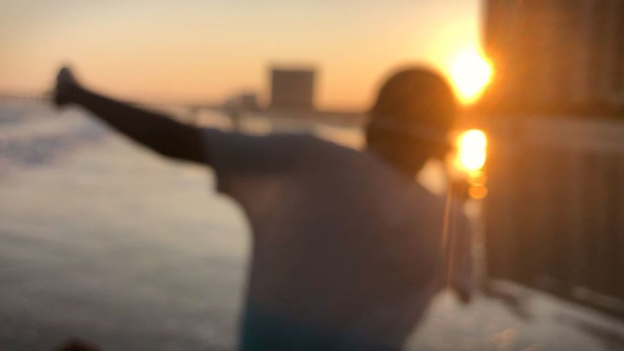 Rear view of silhouette man at beach during sunset
