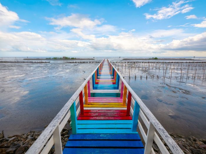View of empty bridge over sea against sky. rainbow bridge and seaside bridge, bright colors.