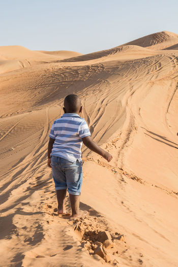 Rear view of boy on sand dune