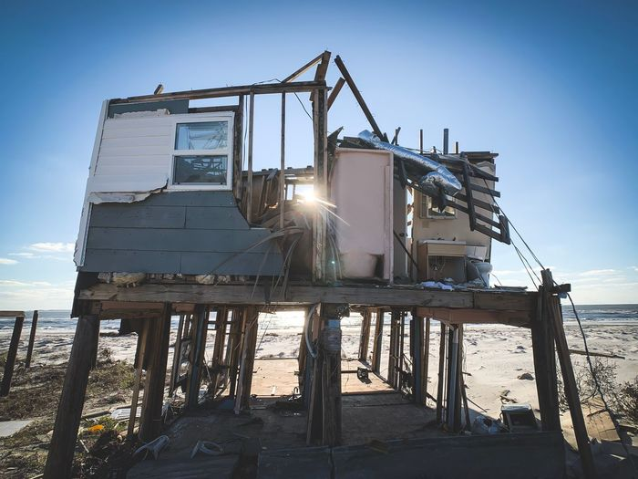 Low angle view of abandoned built structure on beach against sky