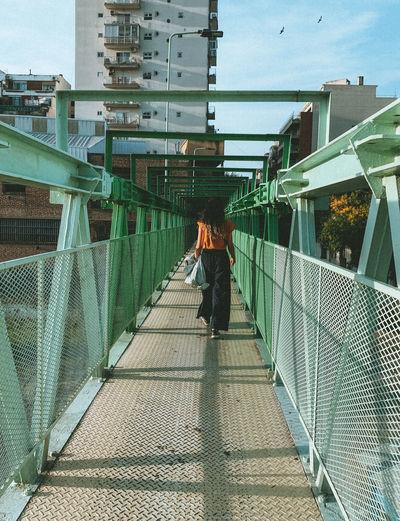 Man walking on footbridge in city