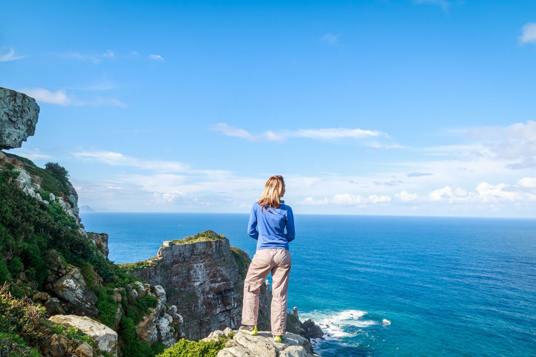 Rear view of woman standing on mountain by sea at cape point