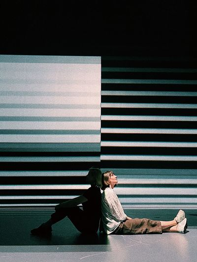 Side view of a woman lying on wall