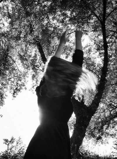 Midsection of man with arms raised against trees