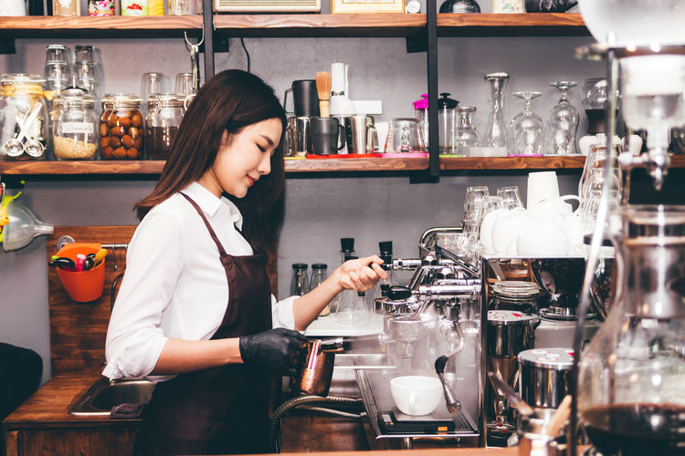Women Barista using coffee machine for making coffee in the cafe Adult Bar - Drink Establishment Bar Counter Bartender Beautiful Woman Business Cafe Coffee Shop Drink Food And Drink Glass Hairstyle Indoors  Occupation One Person Real People Refreshment Standing Three Quarter Length Waist Up Women Young Adult Young Women
