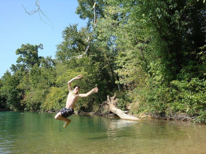 Full length of shirtless man jumping in lake