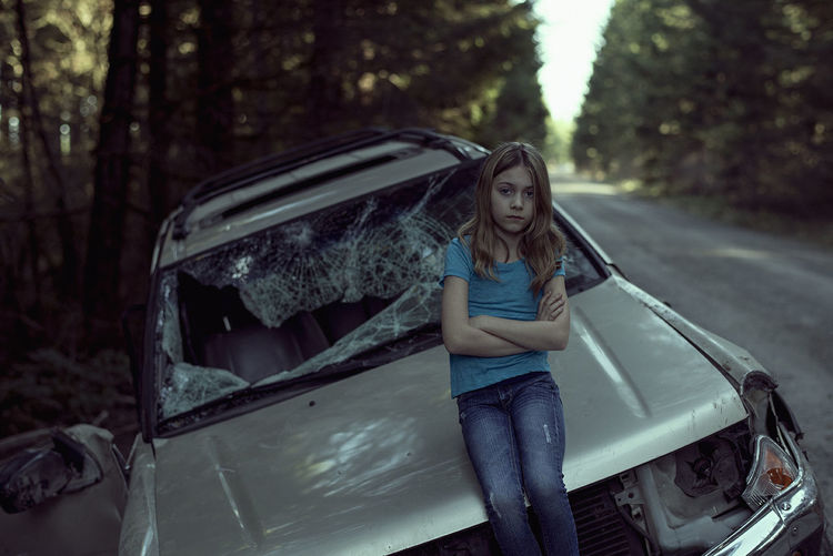 Portrait of girl standing against damaged car