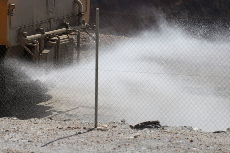 Full-frame view of spray from mining vehicle behind chain link fence
