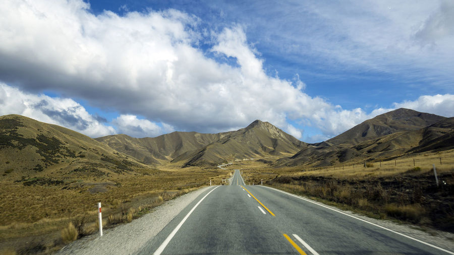 Empty road amidst mountains against sky at lindis pass, new zealand
