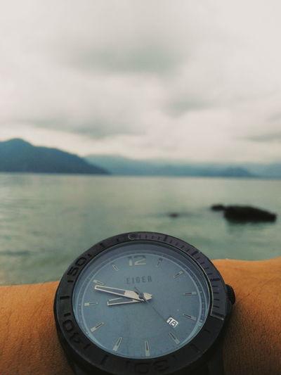 Close-up of clock against sea