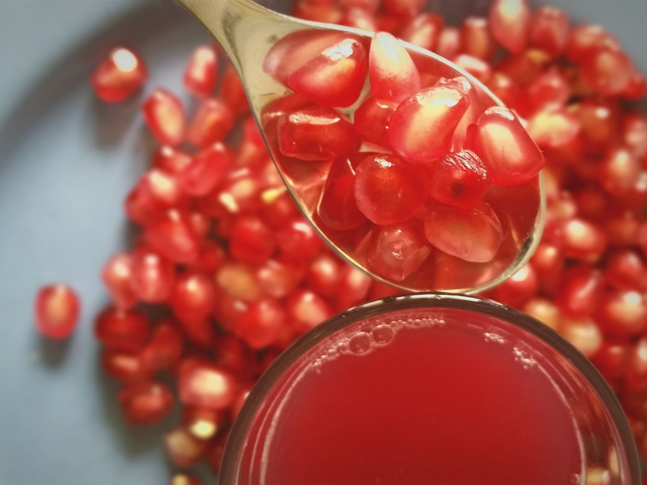 Close-up of pomegranate seeds in spoon over juice