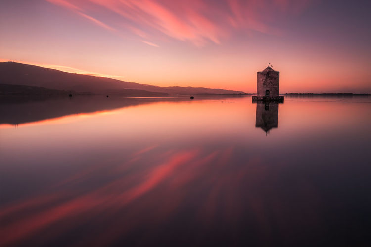 The little windmill in the Orbetello lagoon ay sunset. My Best Photo Architecture Reflection Sea Water Sunset Nature Sky Dusk Tuscany Italy Building Glowing Windmill Twilight Tranquility Dramatic Sky Lagoon Beauty In Nature No People Travel Destinations Tranquil Scene Cloud - Sky Scenics - Nature Lake Idyllic