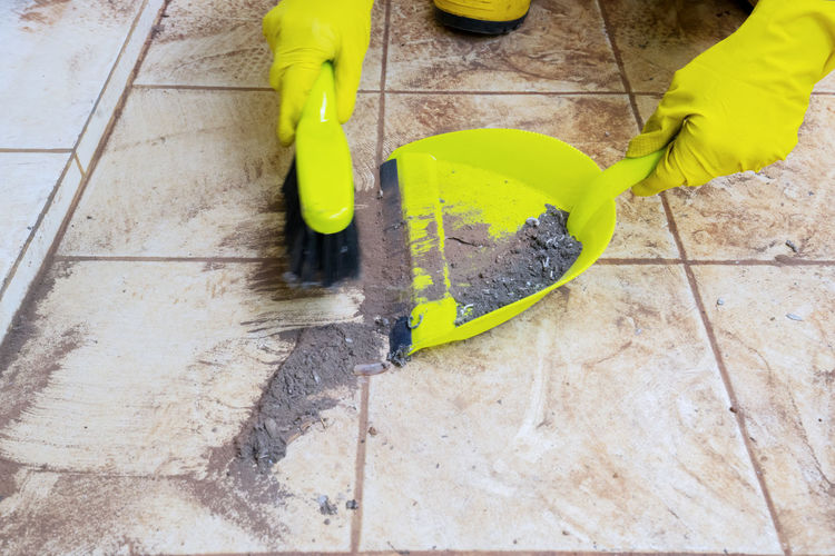Person wearing gloves cleaning dust with duster at home