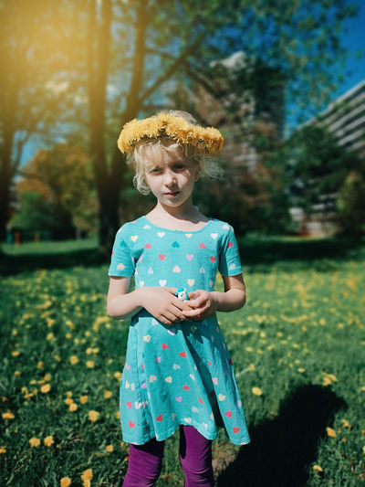 Girl wearing flowers standing on field