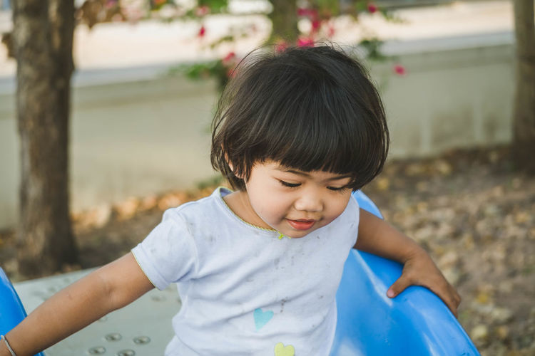Cute girl playing on slide at park