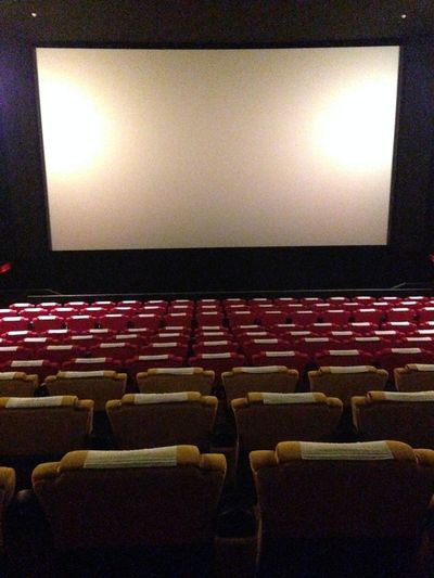 Arts Culture And Entertainment Audience Auditorium Backgrounds Chair Cinema Film Industry In A Row Indoors  MOVIE Movie Theater People Projection Screen Red Seat Theater