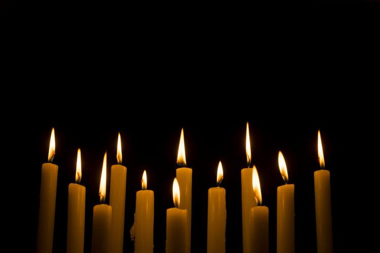 Close-Up Of Illuminated Candles Against Black Background