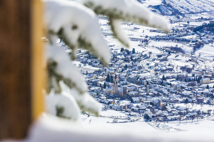 Snow covered landscape against buildings