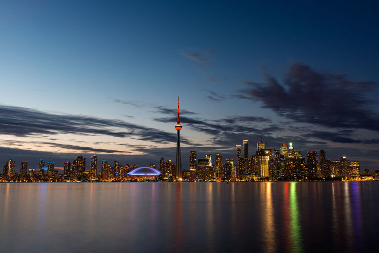 Lake ontario in front of illuminated city against sky